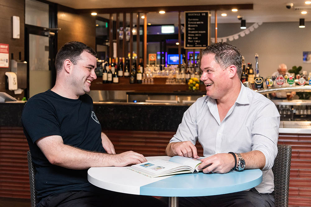 job seeker Jackson sitting on a table inside the settler's tavern bistro smiling alongside manager Adrian Evans looking through a book